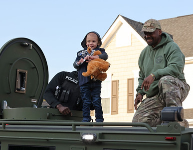 Ford Bartle, 4, looks down at family and friends from the roof of Beaver County's tactical response armored vehicle with Detective Lt. Timmie Patrick during his birthday party Tuesday. Seb Foltz/Butle