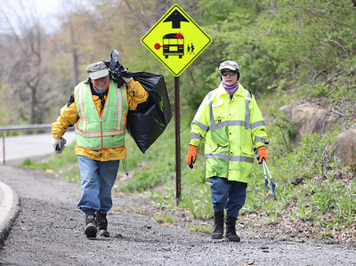 Rick Alexander, 70, carries a bag of litter with his wife Valerie, 67, along Litman Road near the intersection with Route 8. The pair annually have a litter pickup along the stretch of road by their residence. Seb Foltz/Butler Eagle 04/22/21