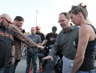 Pastor Brandon Lenhart of the North Main Street Church of God blesses the bike of John Penrod along with Penrod's widow Cheri Penrod (right) and his friends and family. Penrod died in a motorcycle accident in November near Parker. His son, John Penrod Jr. and family friends rebuilt the near totaled bike (pictured). Dozens of motorcycle riders gathered for the annual Blessing of the Bikes celebration at the Crossbow Lounge at Sherwood Lanes in Lyndora Wednesday. Seb Foltz/Butler Eagle 04/07/21