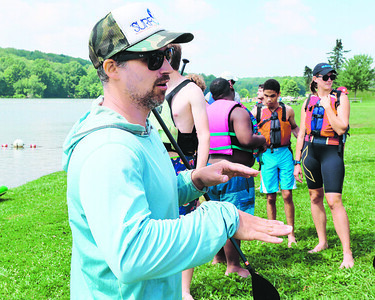 Ian Smith with SurfSUP Adventures gives instructions to visually impaired members of the Envision Blind Sports program Friday at Moraine State Park. Seb Foltz/Butler Eagle 07//30/21