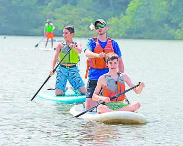 Envision Blind Sports counselor Nate Brown (center) standup paddles with Tanner Cohagan, 13, (front) and Sam Timko Franday at Moraine State Park. Campers from Envision Blind Sports summer program spent the day kayaking and standup paddleboarding with the help of guides. Seb Foltz/Butler Eagle 07/30/21