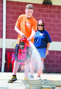 Tanner Dunn, 14, uses a fire extinguisher to douse a propane fire at the Cranberry Twp. Public Safety Training Center Monday, August 2, 2021. Harold Aughton/Butler Eagle.