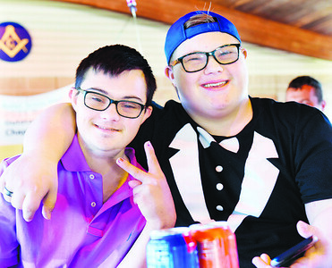 Friends Sam Brown, left, and Aiden Ace celebrate the Butler Senior High School Chapter of the Best Buddies National Chapter of the year award at Alameda Park Monday evening. Harold Aughton/Butler Eagle.