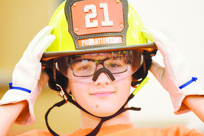 Sam Michel, 14, dons a fire fighter's helmet during a training session at the Cranberry Twp. Public Safety Training Center Monday, August 2, 2021.  Harold Aughton/Butler Eagle.
