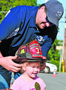 Firefighter Lt. James Senopole lets three-year-old Izabella Reges of Butler try on his fire helmet during the annual National Night Out in the 100 Block of Greenhill Drive in Butler Twp. Tuesday night. Harold Aughton/Butler Eagle.