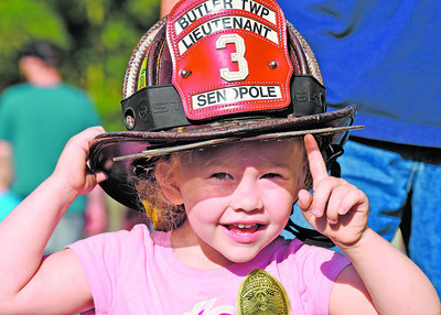 Three-year-old Izabella Reges of Butler tries on Lt. James Senopole's fire helmet during the annual National Night Out in the 100 Block of Greenhill Drive in Butler Twp. Tuesday night. Harold Aughton/Butler Eagle.