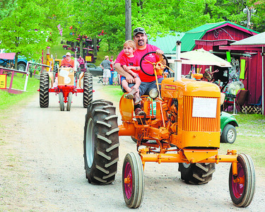 Brad Oros and his daughter Taley, 4, drive to the tractor parade at the Portersville Steam Show Saturday. Seb Foltz/Butler Eagle 07/08/21