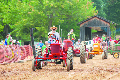 Bill Kinzler and his 1948 McCormick tractor lead a line of tractors in Saturday's tractor parade at the Portersville Steam Show. Seb Foltz/Butler Eagle 08/07/21