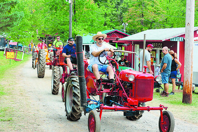 Bill Kinzler and his 1948 McCormick tractor lead a line of tractors to the tractor parade at the Portersville Steam Show Saturday. Seb Foltz/Butler Eagle 08/07/21