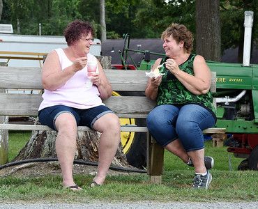 Longtime friends, Becky Kriess of Center Twp., left, and Becky Karns of Butler found time to enjoy a laugh and a cool treat under a shade tree at the Butler Farm Show Monday afternoon. Harold Aughton/Butler Eagle