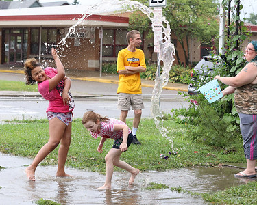 Vilmariyah Vera, 9,(left) and Olivia Nagle, 7, play in a rain puddle with Olivia's mother Amanda Nagle, accross from Emily Brittain Elementary School on West Penn St Tuesday following storms. Seb Foltz/Butler Eagle 08/10/21