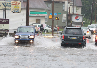 Cars drive through flooded streets on West Cunningham St. Tuesday. Seb Foltz/Butler Eagle 08/10/21