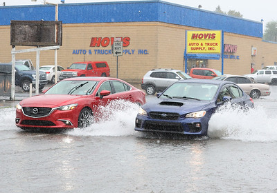 Cars drive through flooded streets on West Jefferson St. Tuesday. Seb Foltz/Butler Eagle 08/10/21