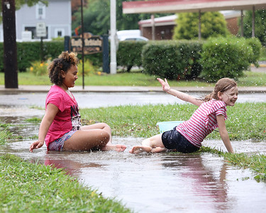 Vilmariyah Vera, 9,(left) and Olivia Nagle, 7, play in a rain puddle accross from Emily Brittain Elementary School on West Penn St Tuesday following storms. Seb Foltz/Butler Eagle 08/10/21