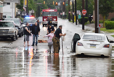 Flash flood waters stranded a driver and his passenger of a white Nissan Maxima along West Penn St. in Butler Tuesday afternoon. Butler police, fire and public works departmen responded to the scene. Harold Aughton/Butler Eagle