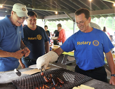 Rotary Club of Rich-Mar volunteers Scott Acree (right), Thomas Kvederis (center) and Gary Weston man the grill during the rotary's annual hot dog rost for the ARC program for adults with disabilities. Seb Foltz/Butler Eagle 08/11/21