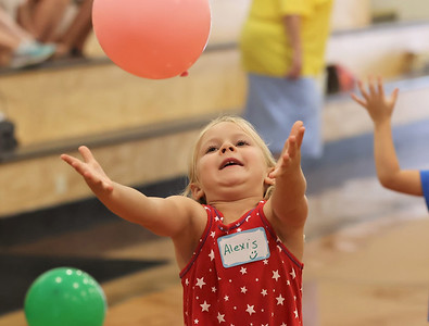 Kindergartener Alexis Brown hits a balloon at one of the activity stations at Butler Catholic's kindergarten kickoff celebration Wednesday. Seb Foltz/Butler Eagle 08/11/21