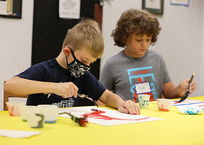 Liam Edwards, 7, and Tyler Culley, 9, work on paint projects at Butler Art Center's Art & Nature Camp Thursday. Campers made paint brushes out of sticks and natural materials like feathers and tree branches in order to do their paintings. The center's week-long camp program focuses on making projects using natural materials. Seb Foltz/Butler Eagle 08/12/21