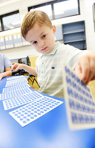 Pre-schooler, Luke Skwirut, 4, uses flash cards to identify letters and numbers at Butler Catholic. Harold Aughton/Butler Eagle