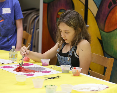 Macie Eichenauer paints  using a brush made of a stick with pine needles at Butler Art Center's Art & Nature Camp Thursday. Campers made paint brushes out of sticks and natural materials like feathers and tree branches in order to do their paintings. The center's week-long camp program focuses on making projects using natural materials. Seb Foltz/Butler Eagle 08/12/21