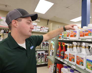 Evans City Road Agway Store Manager Cody Stephenson picks out an example of a fungiside. Seb Foltz/Butler Eagle 07/29/21