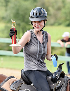 Katie McDonald raises her first place trophy during the horse show competition at the Therapeutic Riding Center in Summit Twp. Saturday. Harold Aughton/Butler Eagle.
