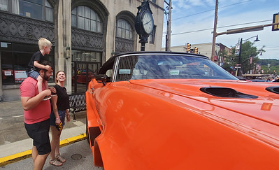 Cruise-A-Palooza-1&2: Three-year-old Howard Bellis admires a monster-truck-like car from the shoulders of Jacob Black of Butler, who stands alongside Howard's mother, Biidaw Morin of Butler, at Sunday's Cruise-A-Palooza on Butler's Main Street. Nathan Bottiger/Butler Eagle