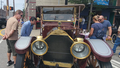 Frank Pascarella of Sarver (Left) and Mike Woddward of Center Township (right) take a look into the engine of an older model of car shown at Sunday's Cruise-A-Palooza on Butler's Main Street. Nathan Bottiger/Butler Eagle