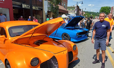 Dan Pernell of Butler stands in front of the three cars he brought to the show while passersby admire them at a glance at Sunday's Cruise-A-Palooza on Butler's Main Street. Nathan Bottiger/Butler Eagle