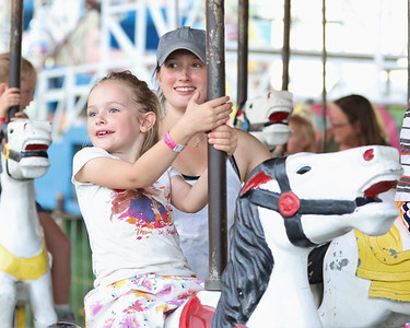 Eva Duffy, 6, and her mother Laura Duffy ride the carousel at the Butler Farm Show Friday. Seb Foltz/Butler Eagle 08/13/21