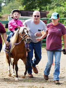 Lelynn Sabich, 4, of Karns City received a little help from her grandfather, Tom Sabich, and volunteers Megan Houston and Lesey Bachman during the horse show competition at the Therapeutic Riding Center in Summit Twp. Saturday. Harold Aughton/Butler Eagle.