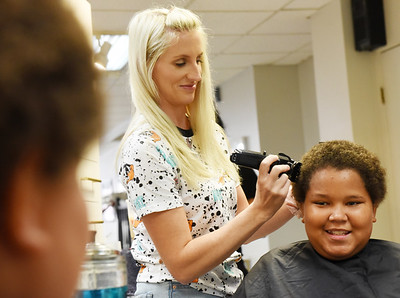 DaShaun Moore, 12, of Butler watches in the mirror as Amber Leech, a volunteer hair stylist from Louis Charles & Co, cuts his hair at the Butler Beauty Academy Monday afternoon. The Beauty Academy was offering free back-to-school haircuts for students. DaShaun will be a sixth grader in Butler Middle School this fall. Harold Aughton/Butler Eagle.