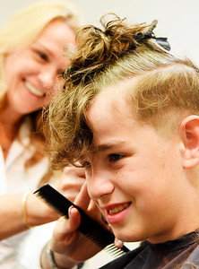 Kaysen Self, 12, of Butler got a little off the side by volunteer hair stylist Kellie Seiler at the Butler Beauty Academy Monday afternoon. The Beauty Academy was offering free hair cuts for back to school. Harold Aughton/Butler Eagle
