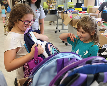 Isabelle Garris, 7, shows off her new panda backpack to Lola Layton, 7, at the Butler YMCA's school supply distribution Wednesday. Seb Foltz/Butler Eagle 08/18/21