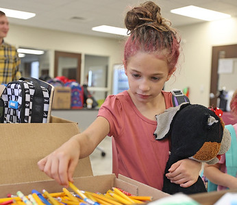 Bella Irvine, 7, of Butler picks out a pencil at the Butler YMCA's school supply distribution Thursday. Seb Foltz/Butler Eagle 08/18/21