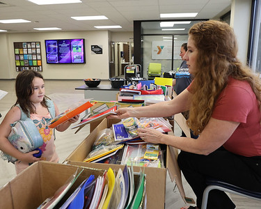 Butler YMCA staff member Heidi Nicholls Bowser hands a notebook to Kendall Schlafhauser, 7, at the facility's school supply distribution Thursday. Seb Foltz/Butler Eagle 08/18/21