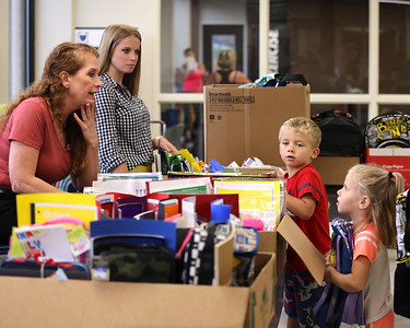 Butler YMCA  staff members Heidi Nicholls Bowser (left) and Brooke Peterson help twins Sevren and Syvette(right) Mesanko, 4, pick out items at building's school supply drive Thursday. Seb Foltz Butler Eagle08/18/21