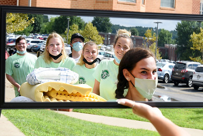 Student volunteers (dressed in green t-shirts), Caleb Covery, Amanda White, Brooke Czerniewski, Kyra Pruszko  strike a pose for Ava Nemchik as they help their fellow students during move in to their dorms at Slippery Rock University. Harodl Aughton/Butler Eagle.
