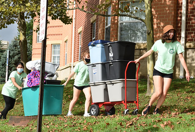 Student volunteers, from left, Natalia Siles, Aimee Campbell, and Tianna Bowser help their fellow students move into their dorms at Slippery Rock University Thursday morning. Harold Aughton/Butler Eagle