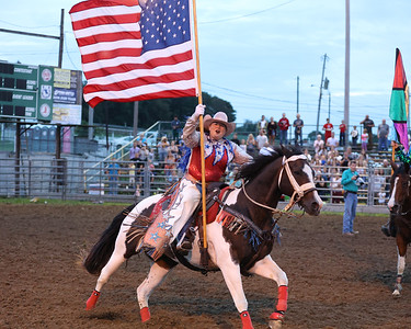 A rodeo performer carries out the American flag to open competition at the North Washington Rodeo Tuesday Evening. Seb Foltz/Butler Eagle 08/17/21
