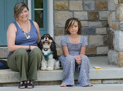 Alison Zawitz and her 8 year old daughter Roree sit in front of their home with their dog Charlotte. Zawitz enrolled her kids in cyber school again this fall out of concern over COVID precautions. Julia Maruca / Butler Eagle