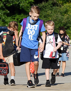 Fourth grader Chris Wilson lends a helping hand to his brother, kindergartner Cannon Wilson, during the first day of school at Rowan Elementary in Cranberry Twp. Wednesday morning. Harold Aughton/Butler Eagle