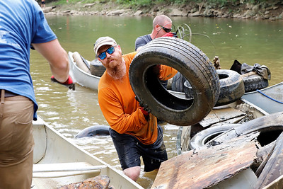 Josh Meeder of Harmony hands off a tire during Saturday's Aquatic Alliance Connoquenessing Creek Cleanup. Seb Foltz/Buter Eagle 09/12/20