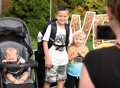Casey Bauer of Butler takes a photo of her nephew, third-grader, Luca Gilleseie with her sons, Tanner, 7 months and Tanner, 2, during the first day of school at Emily Brittain Elementary School Thursday morning.  Harold Aughton/Butler Eagle.