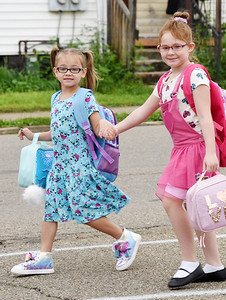 Sisters,  first-grader, Zerina, and second-grader, Amelia Welch hold hands as the head to Emily Brittain Elementary for the first day of school Thursday morning. Harold Aughton/Butler Eagle.