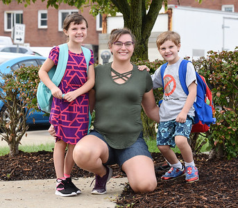 Suzanne Yockey, center, of Butler poses for a photo with her children, Melody, 6, and James, 5, as her husband Mike Yockey takes a photo during the first day of school at Emily Brittain Elementary Thursday morning.  Harold Aughton/Butler Eagle