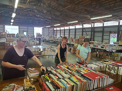 A barn on the Butler Farm Show Grounds will have more than 150,000 books on display next week for a sale benefitting all of Butler County's community libraries. Setting up the sale from left are Karen Pierce, Christy Wilkinson and Addy Wilkinson. EDDIE TRIZZINO/BUTLER EAGLE