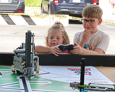 Isaac Friel, 7, helps Ayla Jenkins, 4, control a lego robot at the at the Mars Robotics Association tent at Mars Exploration Celebration Saturday.  Seb Foltz/Butler Eagle 08/28/21