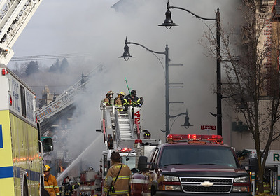 Fire crews from across the region respond to the fire on Main Street in Butler Saturday. The fire allegedly started in the back of Sir Speedy copy center. Seb Foltz/Butler Eagle 01/30/21