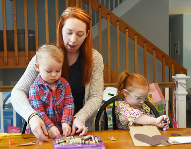 """Wesley Boland, 2, works on his groundhog hand puppet with his mother, Caitlyn Boland, Mars library director, and sister, Emilia, 4, which they made from a """"Take and Make"""" craft bag from the Mars Library. Friday, January 29, 2021. Harold Aughton/Butler Eagle."""